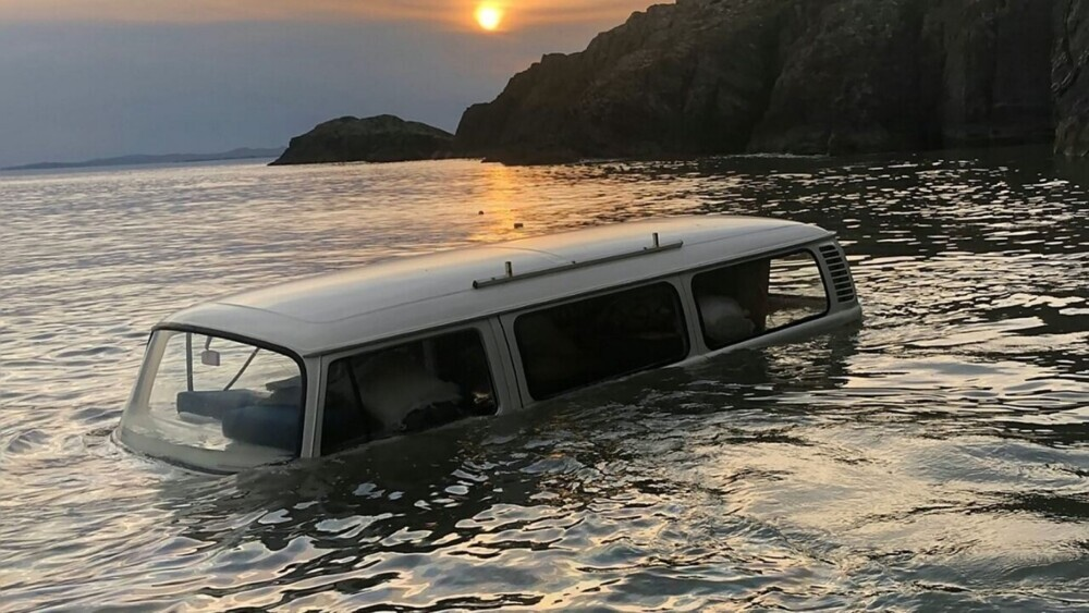 Classic 1978 VW Microbus submerged on beach during high tide